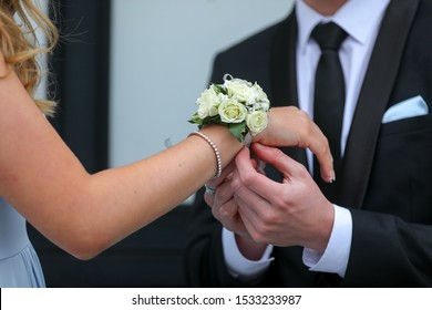 A corsage being placed on a teenagers wrist for a prom date.