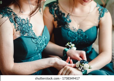 corsage, hands on wrist with flowers on the bride's hand, close up. Girls holding arms out with corsage flowers for prom. Bridesmaid hands corsages. Film noise