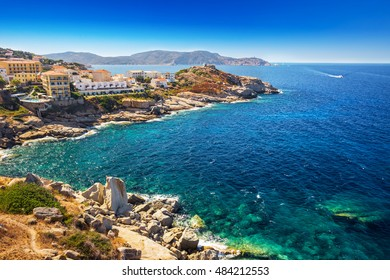 Corsica coastline with historic houses in Calvi old town with turquoise clear ocean water, Corsica, France, Europe.