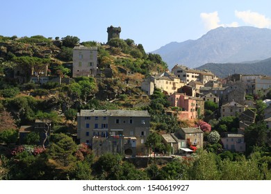 corsica. nonza. mediterranean town in corsica island. corsican hills, the old cittadelle, the genoise tower, mountains in background. daylight, blue sky, some clouds.