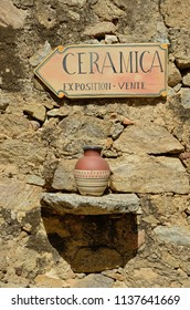 A Corsican jug in the stone wall with a pointer to the ceramic exposition.