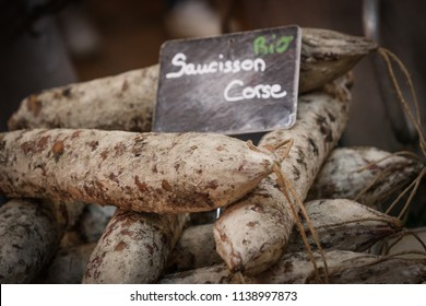 Corsican sausage on the wooden counter at food market, France