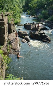 CORSUN-SHEVCHENKIVSKIY, UKRAINE - 24 JULY, 2015: young boys jump from a slope in the river of Ros'. The river of Ros' flows in the Tcherkasy area, Ukraine