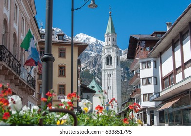 Cortina d'Ampezzo bell tower with flowers in springtime, Dolomites, Italy