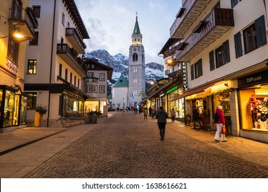 Cortina d'Ampezzo, Italy - February 3 2020: Corso Italia in the Famous Ski Resort Cortina d'Ampezzo on a Winter Evening, the Main Shopping Street in the City Center, with the Spire of the Church