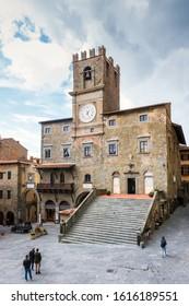 Cortona, Italy - April 11, 2019: Tourists walk through main square Piazza della Repubblica with town hall.