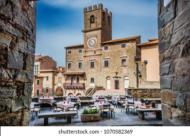CORTONA, ITALY - APRIL 3, 2018: Cortona Communal Palace with renaissance tower clock seen from a narrow street in the historic center, an old medieval town in Tuscany