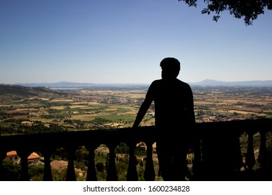 Cortona, Italy. Silhouette of a man against the beautiful landscape of the Arezzo region in Tuscany.