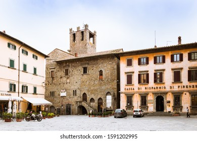 Cortona, Tuscany Italy, 11/14/19: Cityscape with buildings and cars, motorcycle on the square under the blue sky.