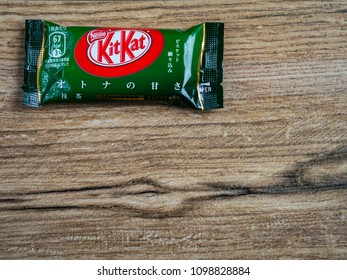 A Coruna, Spain - March 28, 2018 - KitKat Green Tea Chololate Wafer Snack from Japan on wood background with copy space