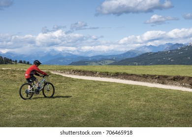 Corvara, Dolomites / Italy -August 18, 2017: Child riding a mountain bike in the meadow
