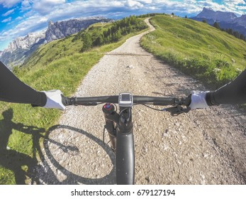 Corvara, Dolomites, Italy. Man riding mountain bike on single trail on a mountain road. POV, original point of view. Fish eye effects