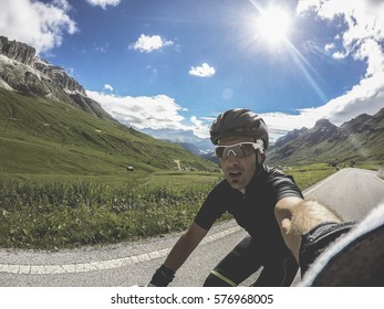 Corvara, Dolomites Italy. Young man on bicycle take a selfie in a beautiful landscape on Pass Pordoi.  Training on road bike on a mountainous road in a Dolomites.