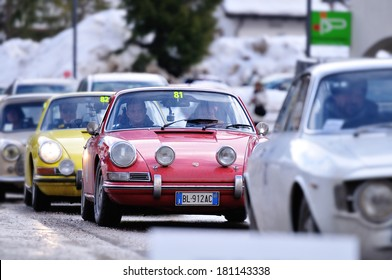 CORVARA, ITALY - FEBRUARY 21: A red Porche 912, a yellow Porsche 911 and other cars take part to the WinteRace classic car race on February 21, 2014 in Corvara. Focus on the red Porsche