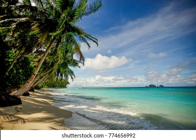 The cosat line of the islands of the mentawai in Indonesia. Beautiful palm trees , white sand and turquoise water on a beautiful windy day with blue sky and white clouds.
