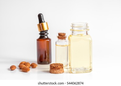 cosmetic almond oil in glass bottle on white background