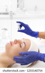 Cosmetic ampoule, a woman in the beauty salon. Vitamin in cosmetic ampoule.