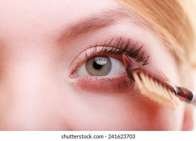 Cosmetic beauty procedures and makeover concept. Closeup part of woman face eye makeup detail. Using comb to separate lashes after applying mascara, long eyelashes.