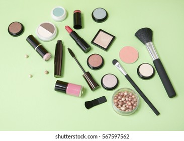 Cosmetic beauty products arranged on a pastel green background