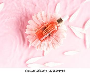 Produit flacon d'huile de sérum de beauté cosmétique sur fond rose dans de l'eau marguerite rose et ondulations. Soins de la peau