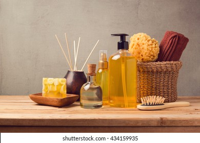 Cosmetic body care and spa products on wooden table over grey background