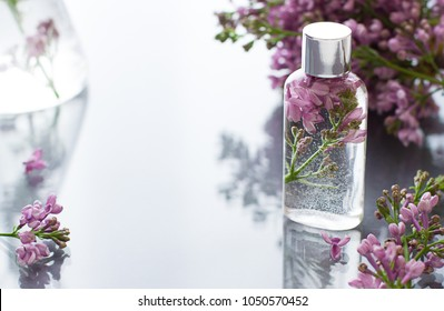 Cosmetic bottle close up with lilac flowers