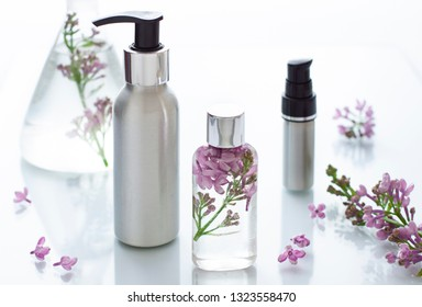 Cosmetic bottle close up with lilac flowers on the white background