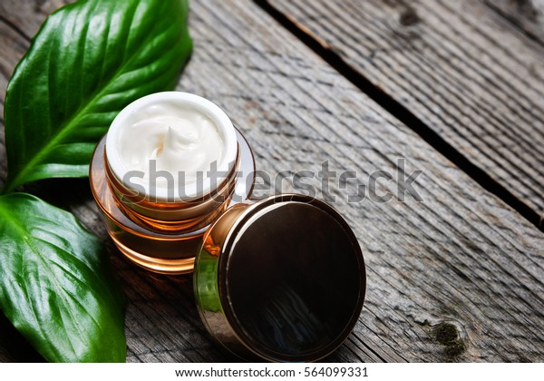 Cosmetic bottle container with green herbal leaves, Blank label for branding mock-up, Natural beauty product concept. Copyspace.