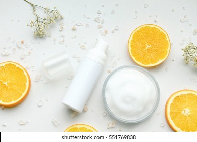 Cosmetic bottle containers with fresh orange slices, Blank label for branding mock-up, Natural Vitamin C beauty product concept.