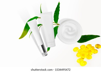Cosmetic bottle containers with green herbal leaves, Blank label for mock-up. Natural beauty product concept on white background with copy space for text. Flat lay composition, top view