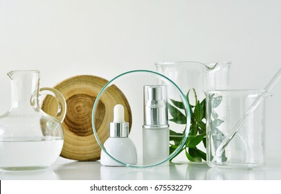 Cosmetic bottle containers with green herbal leaves and scientific glassware, Focus on blank label package for branding mock-up, Research and develop natural organic beauty skincare product concept.