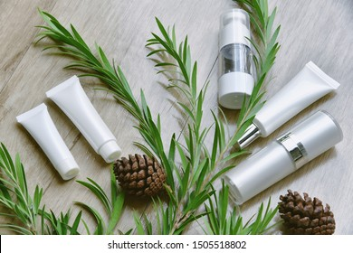 Cosmetic bottle containers packaging with green herbal leaves, Blank label for organic branding mock-up, Natural skincare beauty product concept.