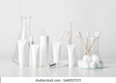 Cosmetic bottle containers and scientific glassware, Blank package for branding mock-up, Pharmaceutical skincare by dermatologist doctor, Research and develop beauty product concept.