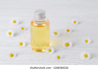 a cosmetic bottle with fresh chamomile flowers, selective focus