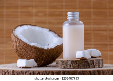 cosmetic bottle and fresh organic coconut , natural background