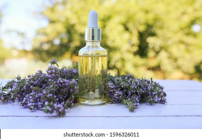 cosmetic bottle with a pipette and lavender oil lies on a wooden table next to delicate lilac fragrant flowers in a Sunny garden