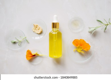 cosmetic bottle with a pipette on a background with medical glasses, natural ingredients and different cosmetic textures. cosmetics production concept with natural ingredients