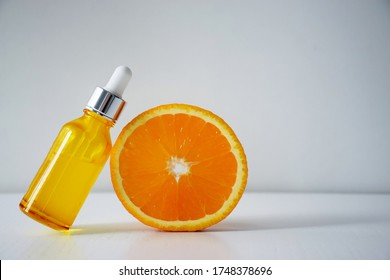 Cosmetic bottle with Vitamin C serum and half of orange on white background. Citrus essential oil, cosmetics aromatherapy. Organic SPA cosmetics with herbal ingredients.
