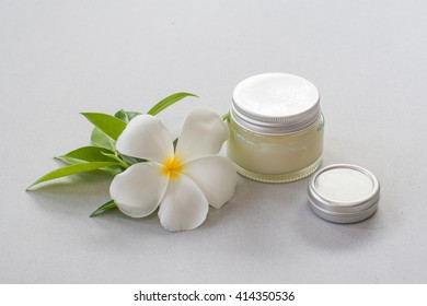 cosmetic box and cosmetic cream isolated on gray background with frangipani flower
