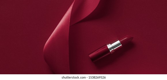 Cosmetic branding, glamour lip gloss and shopping sale concept - Luxury lipstick and silk ribbon on maroon holiday background, make-up and cosmetics flatlay for beauty brand product design
