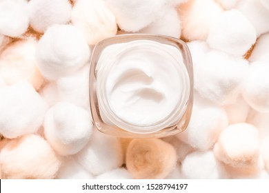 Cosmetic branding, moisturizing emulsion and facial care concept - Luxury face cream for sensitive skin and orange cotton balls on background, spa cosmetics and natural skincare beauty brand product
