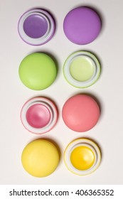 cosmetic bright macaroons lying in row, sweet lip balms on white background,  closed and opened cans, isolated cosmetic photo