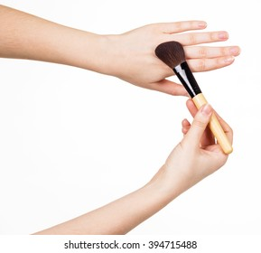 Cosmetic brush for makeup in the hands of women isolated on white background.