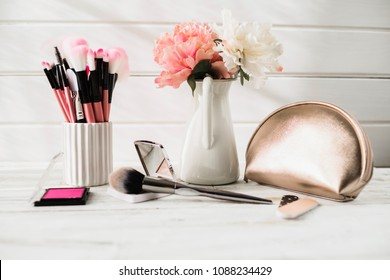 Cosmetic brushes with bouquet on light dressing table on wooden background