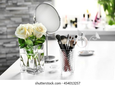 Cosmetic brushes with bouquet on light dressing table