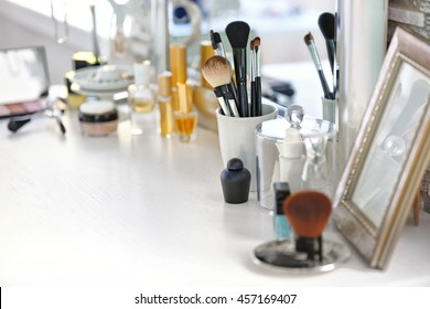Cosmetic brushes in cup on light dressing table