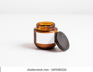 cosmetic or candle, dark amber glass bottles with cover, isolated white background. Closeup, minimal brand packaging mock up, can also be used for honey or hazelnut, peanut butter.