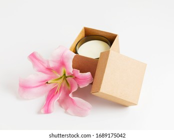 a cosmetic or candle inside a cardboard box package with a flower, on white background. Environmentally friendly gift. Zero waste