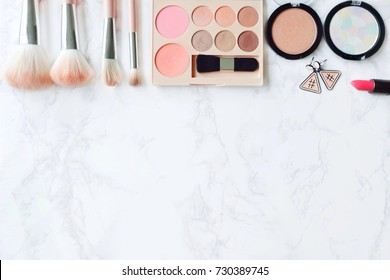 Cosmetic Composition. Pink brush set, lipstick, earring, blush on and  eyeshadow palette on marble table. Cosmetic dressing table for women make up concept. Flat lay, top view. Copy space.