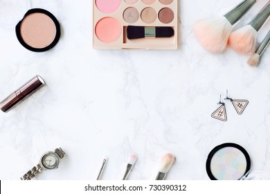 Cosmetic Composition. Pink brush set, lipstick, earring, blush on, watch and  eyeshadow palette on marble table. Cosmetic dressing table for women make up concept. Flat lay, top view. Copy space.